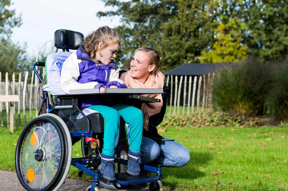 Disability support worker with young girl in wheelchair